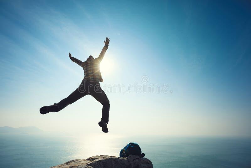 Hiker jumping on sunrise seaside cliff edge. Female hiker jumping on sunrise seae cliff edge royalty free stock photography