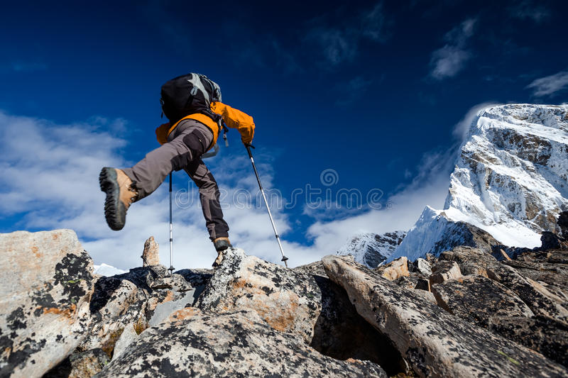 Hiker jumps in mountains stock photography