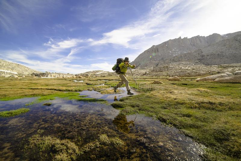 Hiker jumps over creek in sierra nevadas royalty free stock images