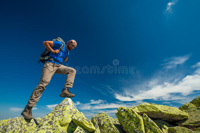 Hiker jumps over stones stock photography