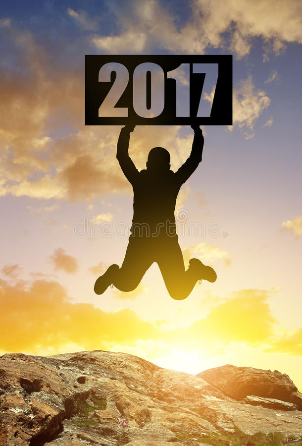 Hiker jumps up in celebration of the New Year 2017. royalty free stock images