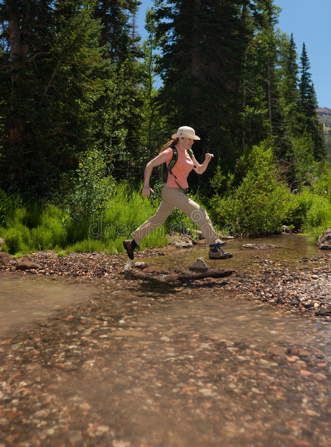 Hiker leaping over stream