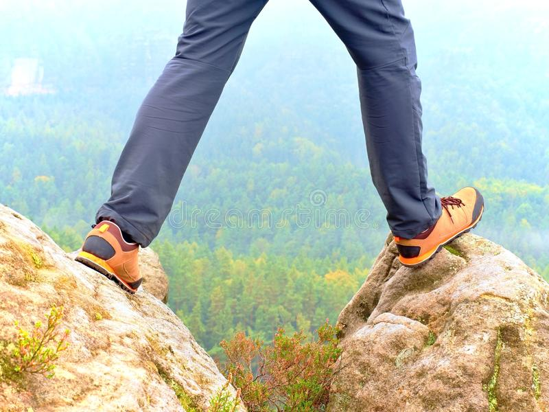 Hiker legs in comfortable trekking boots on rock. Man legs in light outdoor trousers, leather shoes. Hiker legs in comfortable trekking boots stand on rocky peak royalty free stock photo