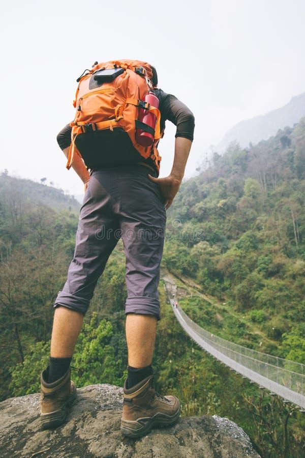 Hiker legs standing on rock. Hiker standing on rock with mountain suspension footbridge near stock photo