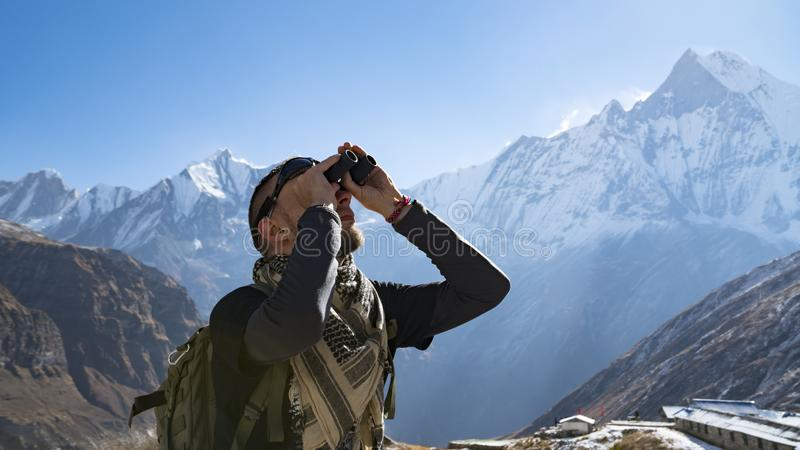 Hiker looking through binoculars on a trekking trail to the Annapurna base camp, the Himalayas, Nepal. Himalayas royalty free stock images