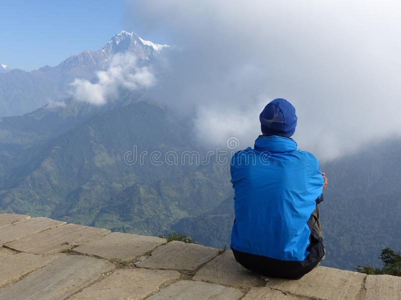 Hiker looking to the mountain on Poon Hill, Dhaulagiri range, Ne royalty free stock photography