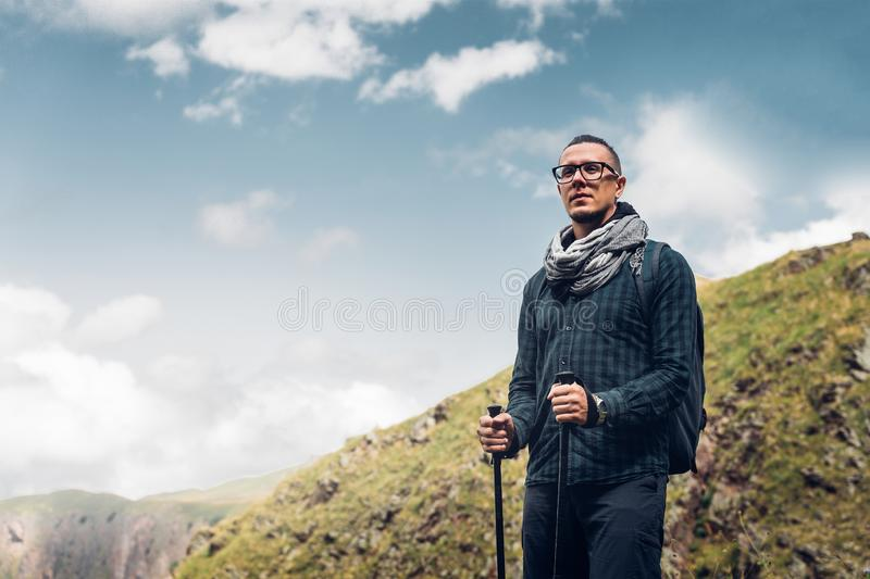 Hiker Man With Backpack And Trekking Poles Resting And Looking A. T The Mountains In Summer Outdoor, Rear View. Adventure Hiking Concept stock photo