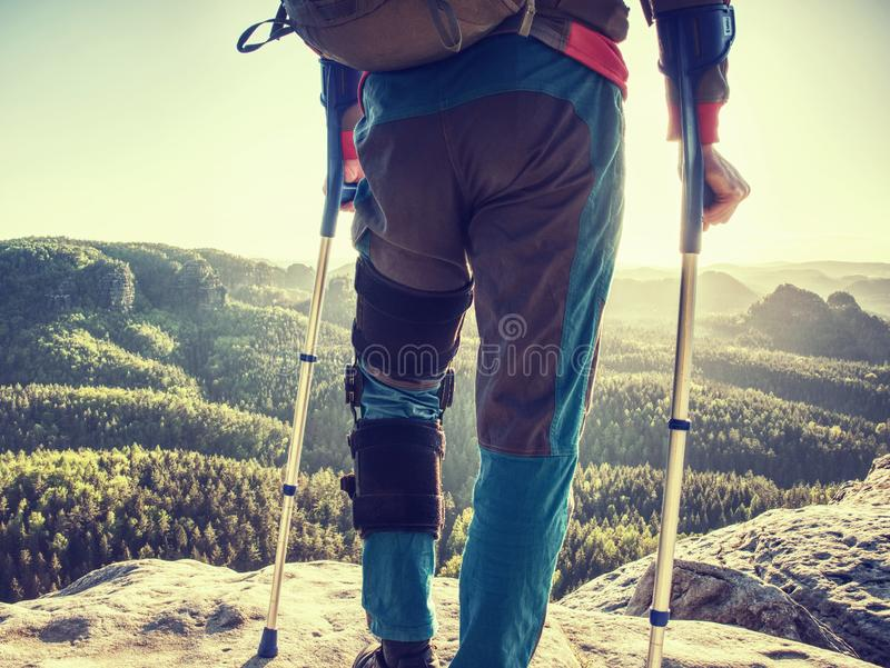 Hiker man with broken leg in immobilizer and crutches royalty free stock images