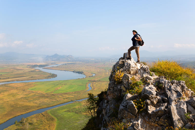 Hiker man climbed a mountain and admire nature stock photography