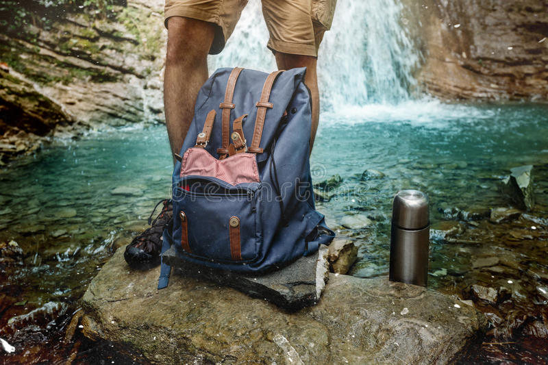 Hiker Man Feet, Backpack And Thermos On Waterfall Background Adventure Hiking Travel Concept. Adventure Hiker Man Feet, Backpack And Thermos On Waterfall stock photo