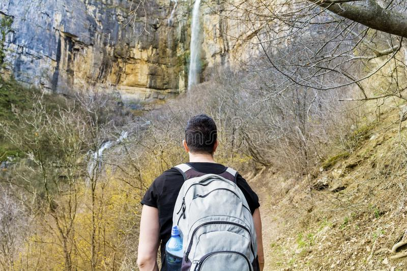 Young Man in a High Mountain looking Big Waterfall stock photography