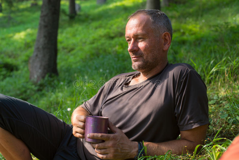 Hiker man is resting, lying on the green grass with cup of coffee, thinking about something. royalty free stock image