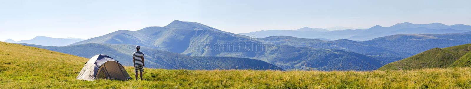 Hiker man standing near camping tent in carpathian mountains. To royalty free stock image