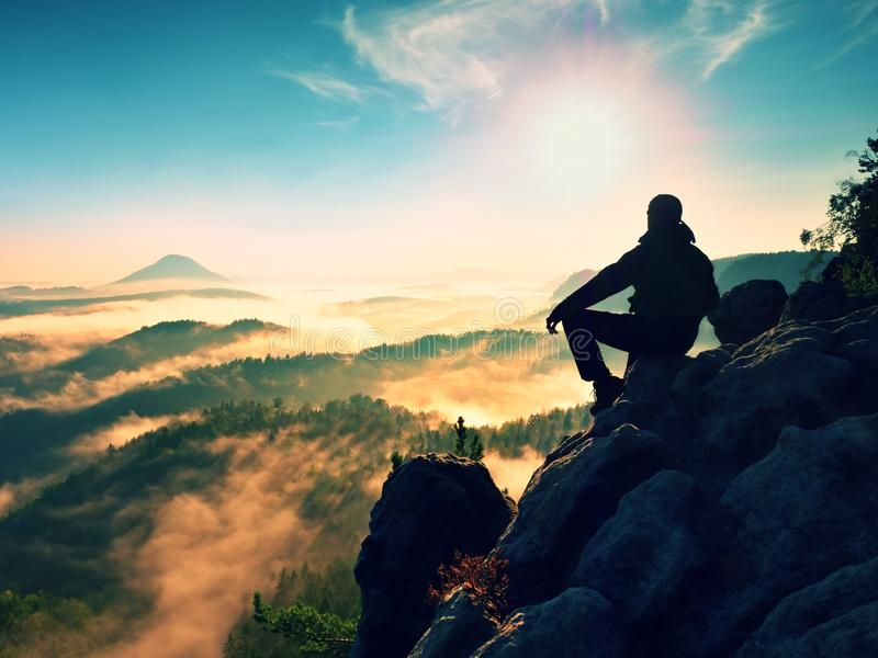 Hiker man take a rest on mountain peak. Man lay on summit, bellow autumn valley. Bright morning Sun shining in sky stock photo