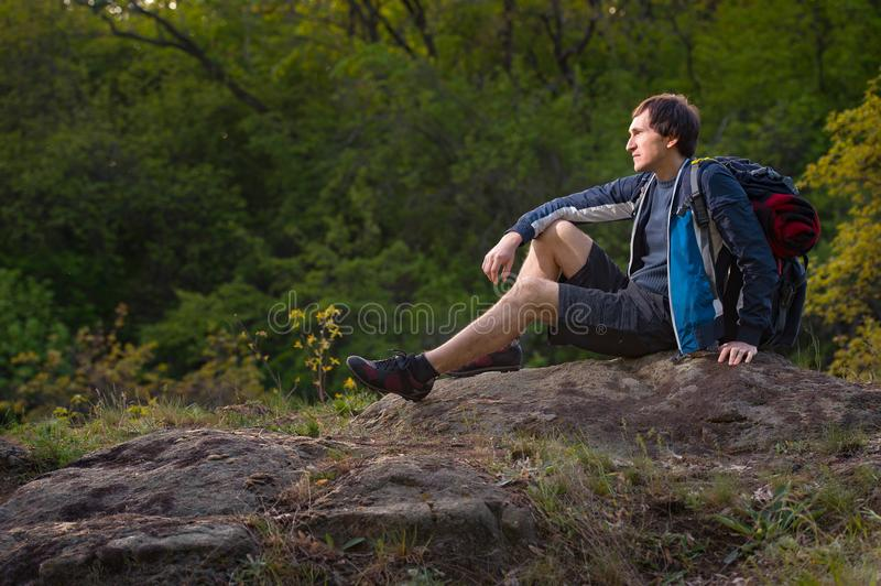Hiker man takes a rest during summers expedition. Travel, vacation, holidays and adventure concept. stock images