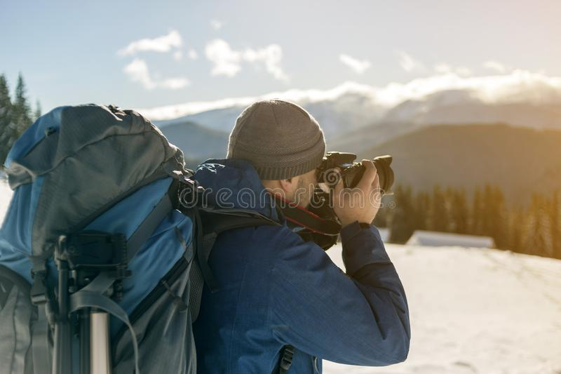 Hiker man tourist photographer in warm clothing with backpack and camera taking picture of snowy valley and woody mountain peaks royalty free stock images