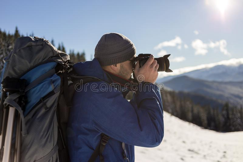 Hiker man tourist photographer in warm clothing with backpack and camera taking picture of snowy valley and woody mountain peaks stock images
