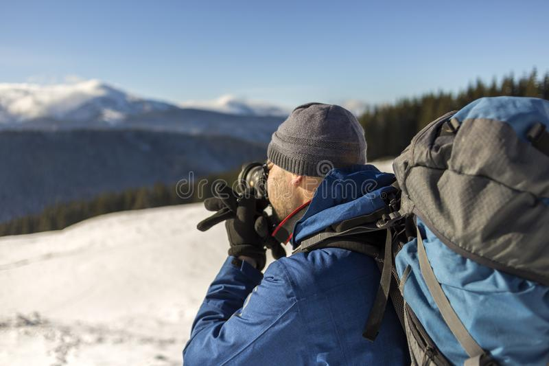 Hiker man tourist photographer in warm clothing with backpack and camera taking picture of snowy valley and woody mountain peaks royalty free stock photo