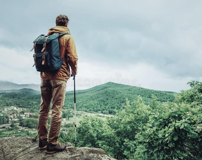 Hiker man with trekking poles. Hiker young man with backpack and trekking poles standing on edge of cliff and looking at the mountains royalty free stock photography