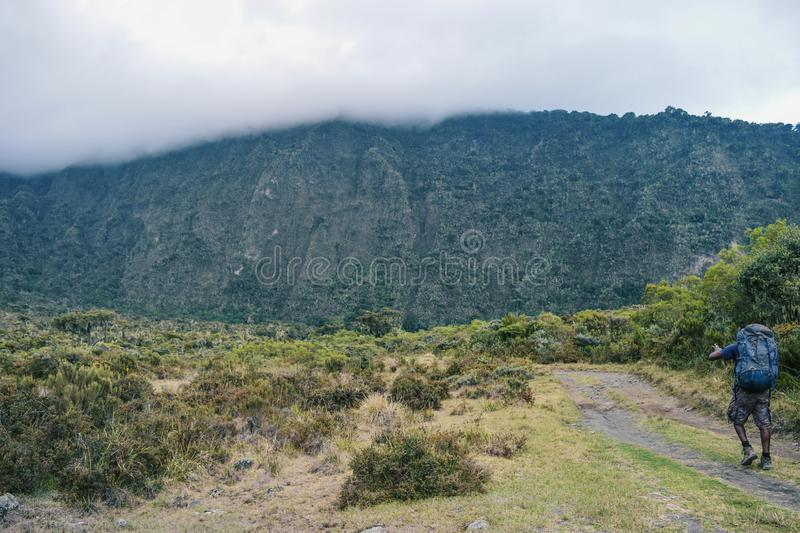 A hiker at Mount Meru, Tanzania. A hiker against a foggy mountain background at Mount Meru, Arusha National Park, Tanzania royalty free stock photo