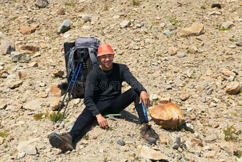 Hiker nas montanhas parado alpinista com mochila imagens de stock royalty free