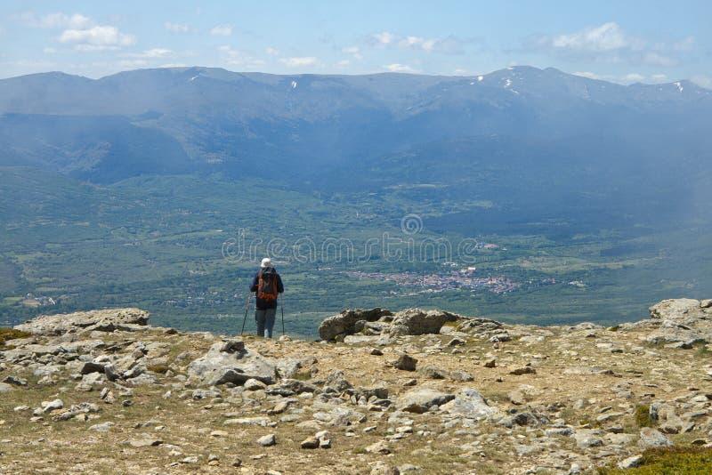 Hiker observa un pueblo desde una cima de montaña con un paisaje montañoso al fondo fotos de archivo