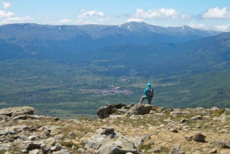 Hiker observa un pueblo desde una cima de montaña con un paisaje montañoso al fondo imagenes de archivo