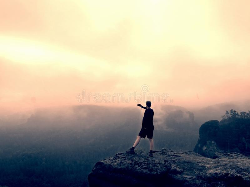 Hiker in pants is taking photo on the rocky peak at sunrise. Mist in rocky mountains royalty free stock photo
