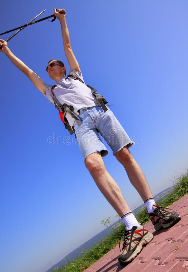 Hiker with raised arms and trekking sticks royalty free stock photography