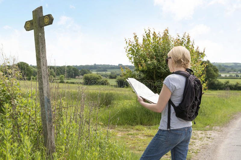 Hiker Reading Map Beside夫人路标户外 免版税图库摄影