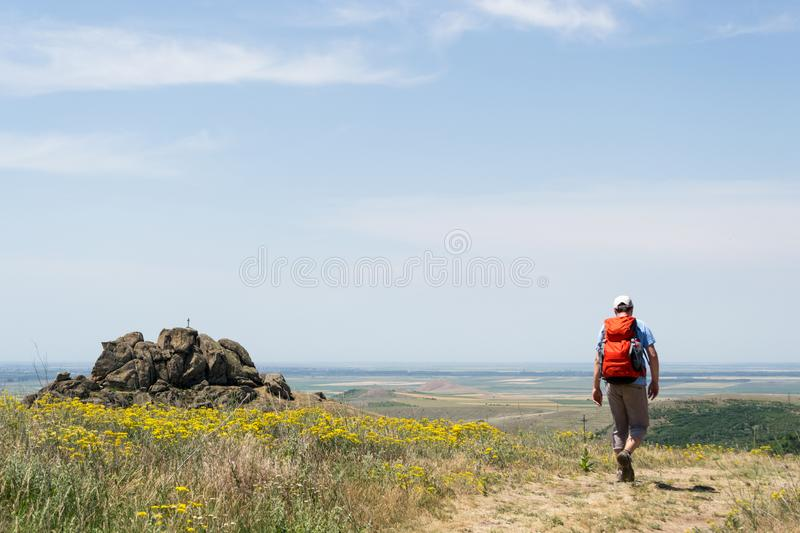 Hiker with a red backpack on a trail with yellow flowers, in Macin Mountains, oldest mountains in Romania royalty free stock photos