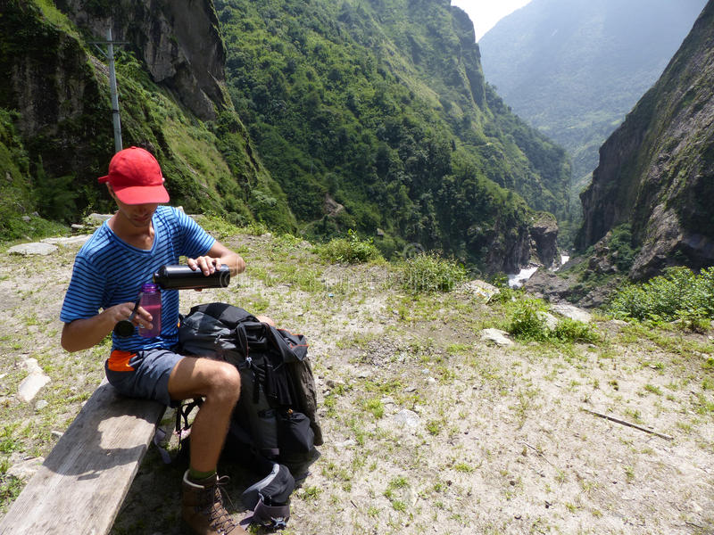 Hiker relaxing on bench. Marsyangdi river valley - Lovely valley on Annapurna circuit trek in Nepal stock photography