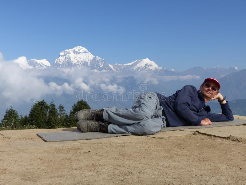 Hiker relaxing on Poon Hill, Dhaulagiri range, Nepal royalty free stock images