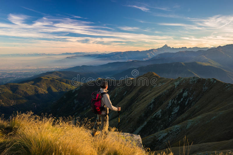 Hiker resting on the mountain top. Hiker relaxing on the mountain summit at sunset and looking at majestic panorama of the italian Alps in autumn season. Wide royalty free stock images