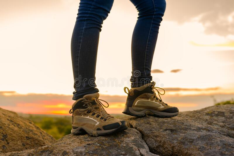 Hiker`s Legs on the Rocky Trail at Summer Sunset. Travel and Adventure Concept. stock images