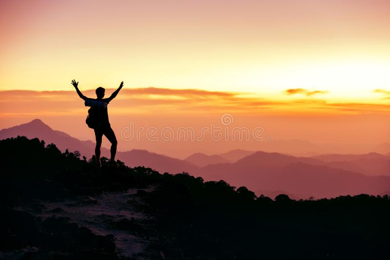 Hiker`s silhouette stands on mountain top against sunset. Hikers or travelers silhouette stands on mountain top against sunset with raised arms stock photos