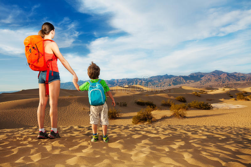 Hiker with selfie stick and son, Death valley. Young women hiker with son young boy looking at death valley stock photos