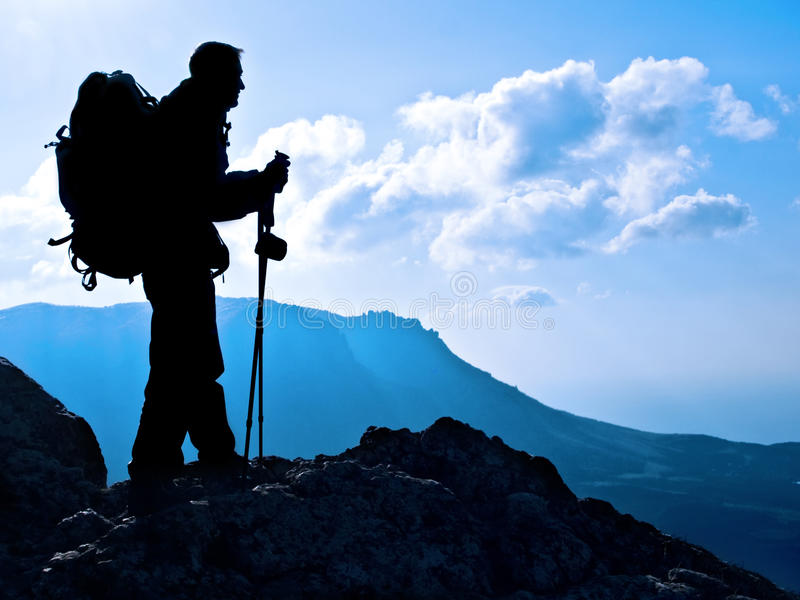 Hiker silhouette. Hiker on top, silhouetted in high mountains royalty free stock photo