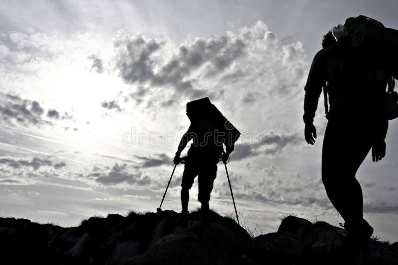 Hiker silhouette. Silhouette of two hikers on a mountain ridge stock photos