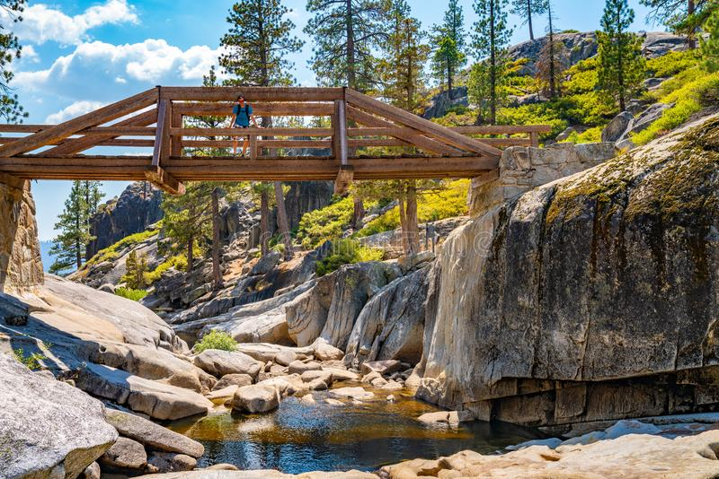 Hiker sitting on a bridge across a dried out Yosemite waterfall. stock images