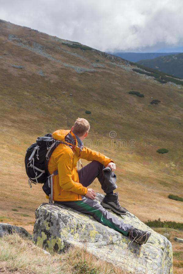 Hiker sitting on rock builder in mountains stock images