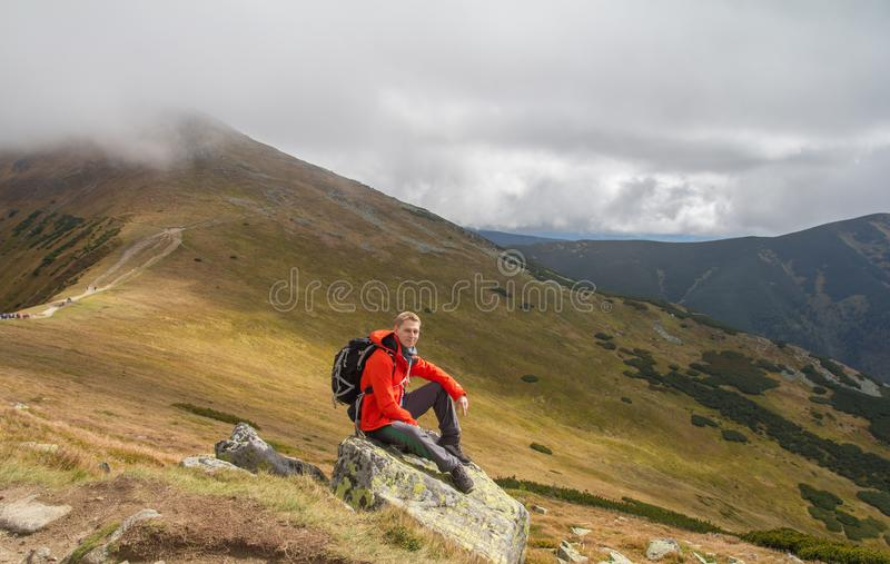 Hiker sitting on rock builder in mountains stock photos