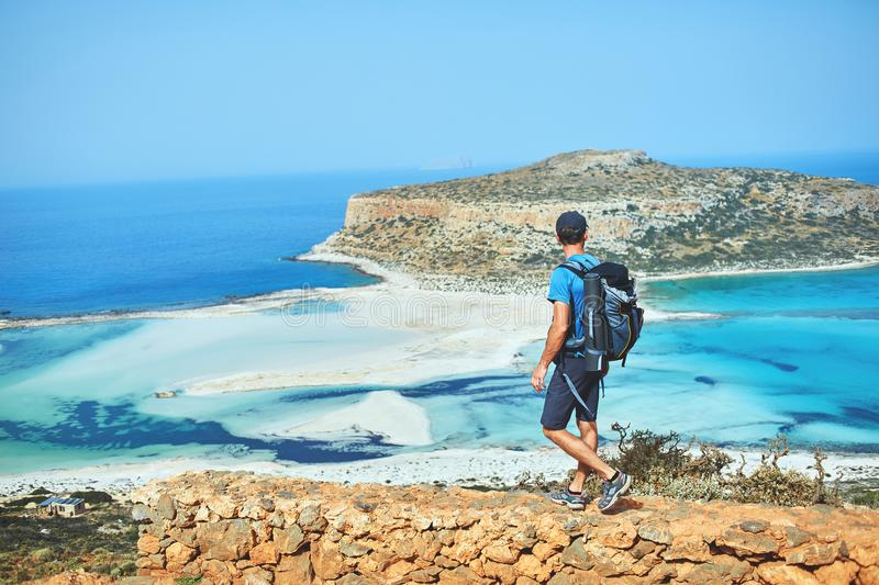 Hiker with small backpack on the trail to the Balos beach. Back view of hiker with small backpack on the trail to the Balos beach at early morning. Balos beach stock photography