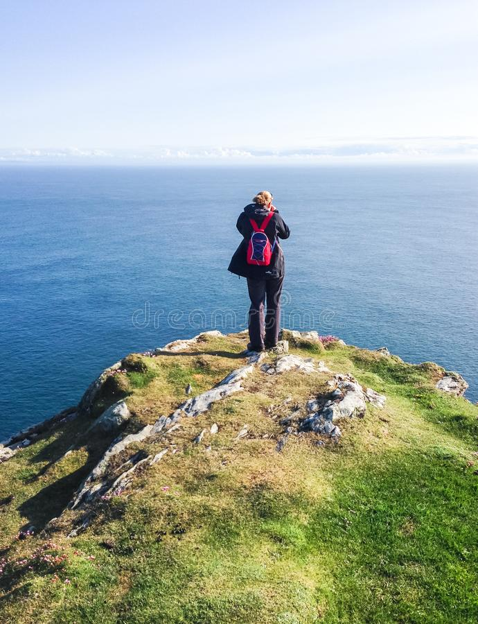A hiker stands at a coastal cliff in Scotland stock photo