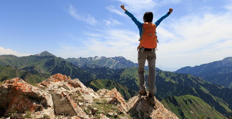 Hiker stand at cliff edge on mountain top. Successful Hiker outstretched arms stand at cliff edge on mountain top royalty free stock photography