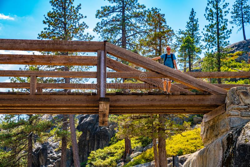 Hiker standing on a bridge across a dried out Yosemite waterfall. royalty free stock photo