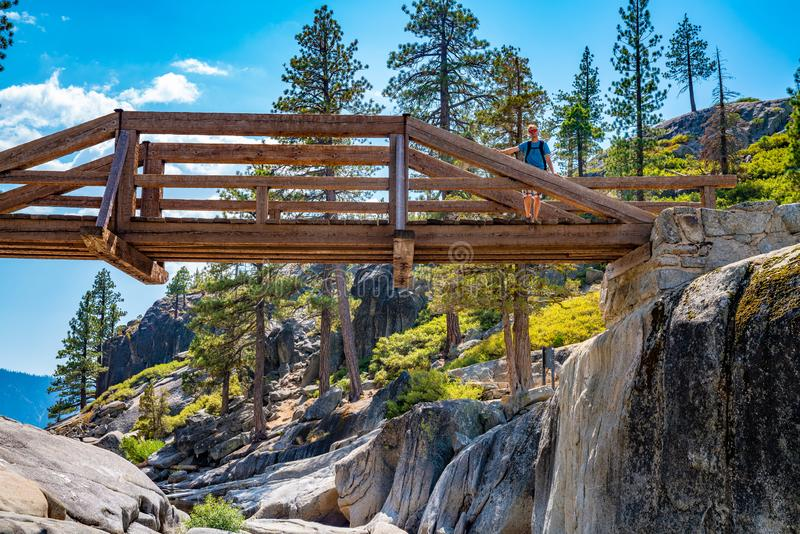 Hiker standing on a bridge across a dried out Yosemite waterfall. royalty free stock photography