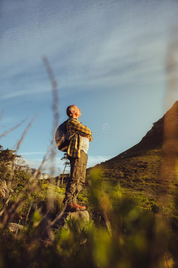 Hiker standing on a hill looking at the hills around stock photography