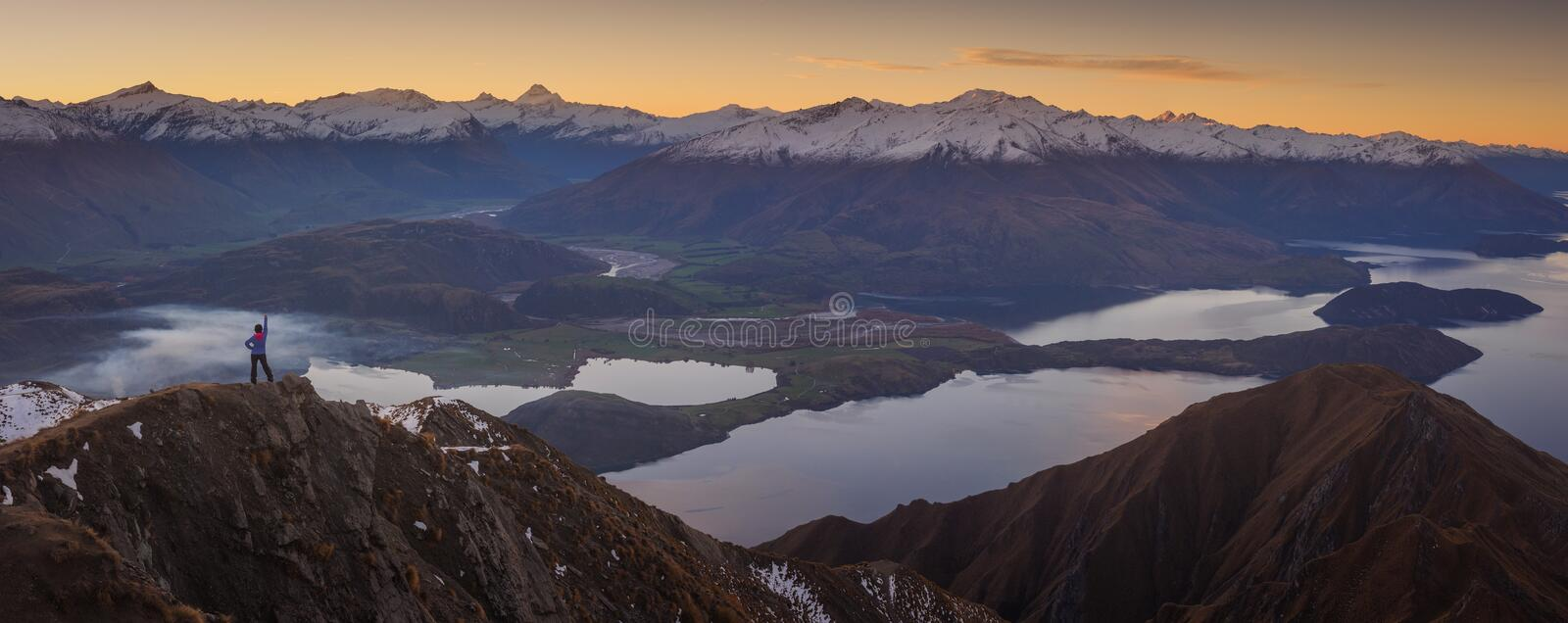 Woman hiker standing on a ledge of a mountain, enjoying the beautiful sunrise royalty free stock photography