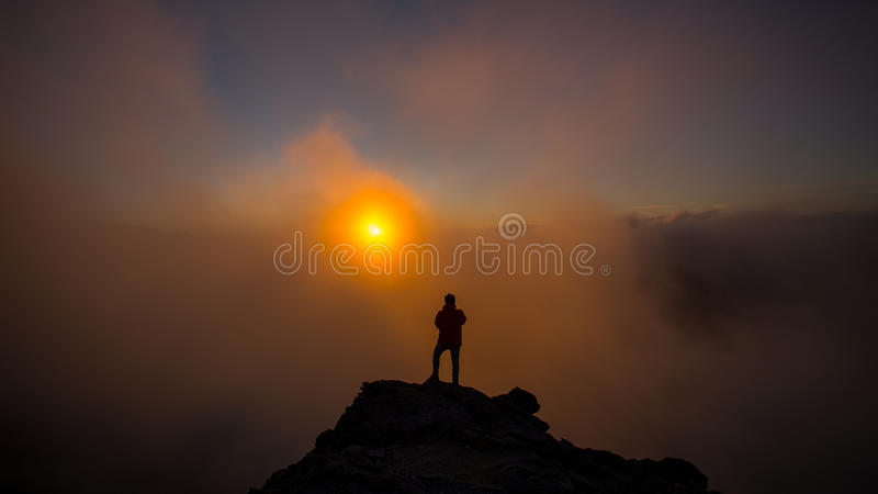 The Photographer Taking Pictures on the Mountain with Clouds Dur stock images